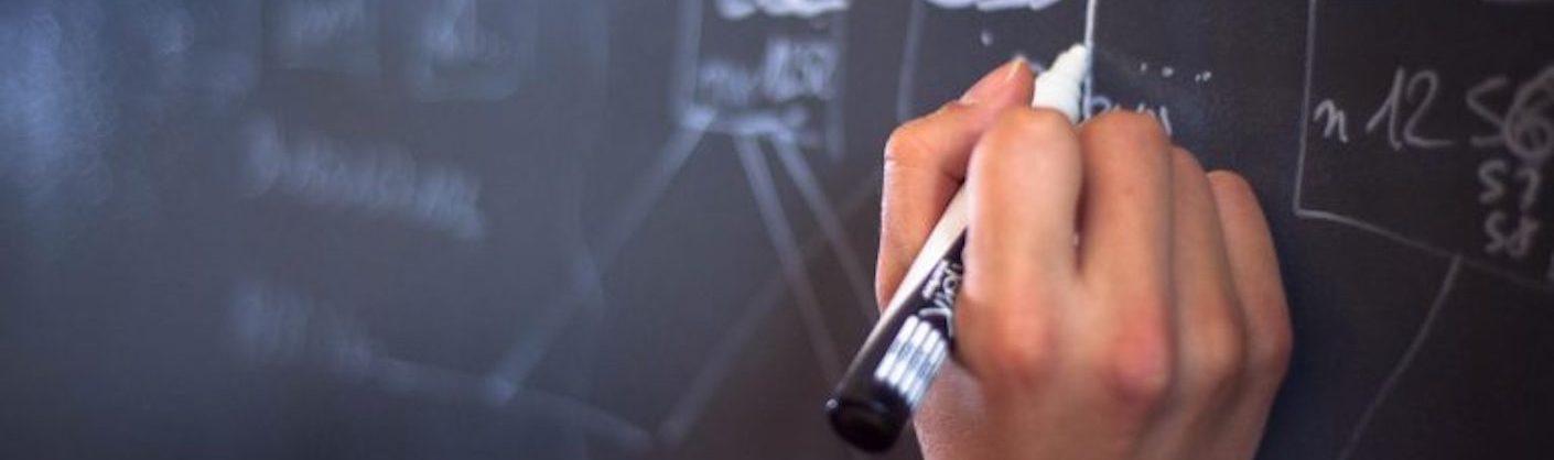 main écrivant sur un tableau